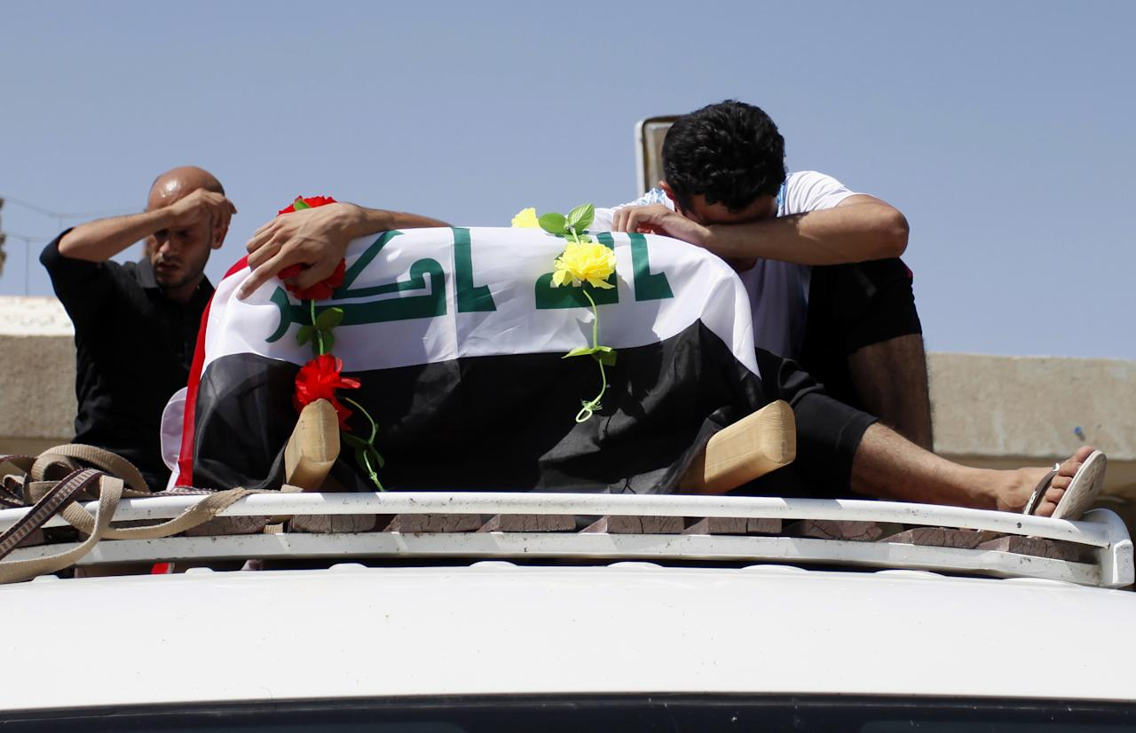 Relatives of an Iraqi woman who was killed along with her husband in a car bomb attack during their honeymoon, her family said, grieve over her coffin during the funeral in the Shiite holy city of Najaf, 100 miles (160 kilometers) south of Baghdad, Iraq, Sunday, Aug. 11, 2013. A wave of car bombings targeting those celebrating the end of Ramadan across Iraq killed scores of people Saturday, a bloody reminder of the inability of Iraqi authorities to stop violence threatening to spiral out of control. (AP Photo/Haider Hamdani)