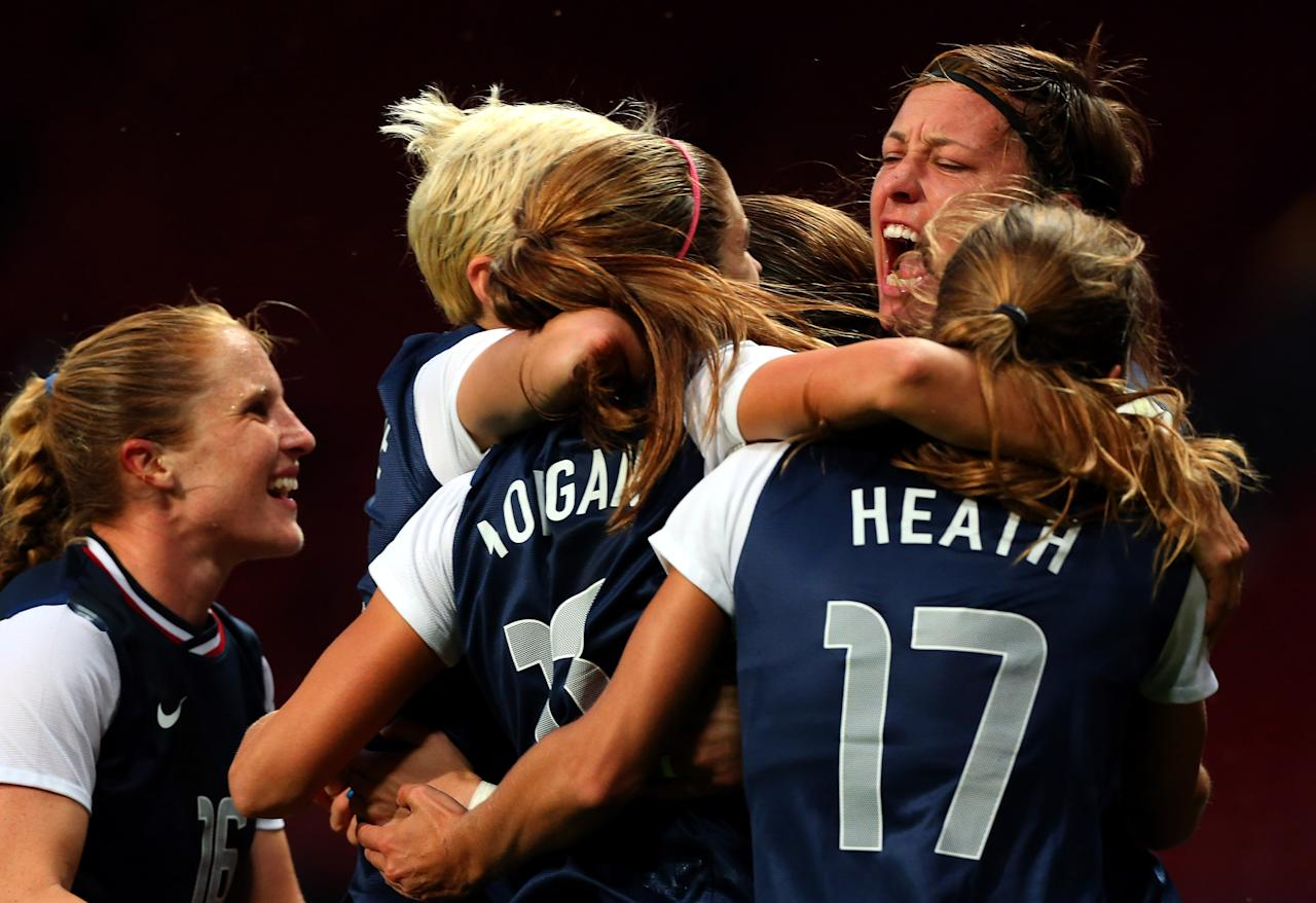 Alex Morgan #13 of the United States celebrates with her team-mates after scoring the winning goal in extra time during the Women's Football Semi Final match between Canada and USA, on Day 10 of the London 2012 Olympic Games at Old Trafford on August 6, 2012 in Manchester, England.  (Photo by Stanley Chou/Getty Images)