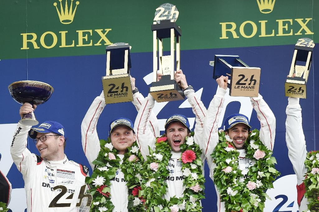 (L to R) Porsche Motorsport chief Andreas Seidl and the three drivers of the Porsche 919 Hybrid N°2 -- Marc Lieb, Romain Dumas and Neel Jani -- celebrate after winning the Le Mans 24 Hour endurance race, on June 19, 2016 (AFP Photo/Jean-Sebastien Evrard)