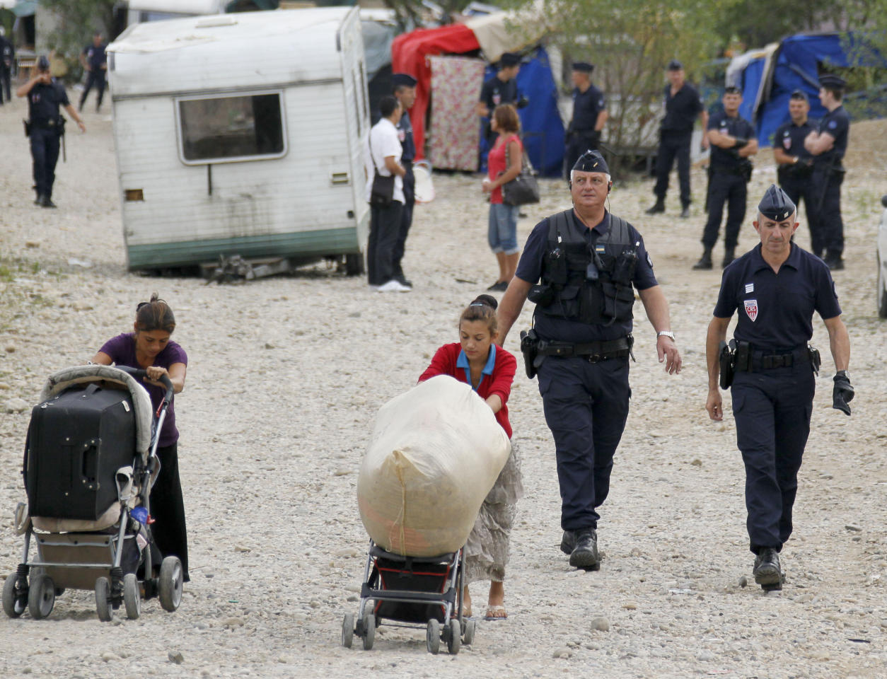 """French CRS police evacuate families and remove their caravans from an illegal camp housing about 114 Roma, referred to as """"Gens du Voyage"""", in Saint-Priest, near Lyon, Southeastern France, August 28, 2012. The French Interior minister said on Monday he would ask Romania and Bulgaria to do more to integrate their Roma minorities as the new government in Paris grapples with how to handle Roma immigrants in France.   REUTERS/Robert Pratta   (FRANCE - Tags: SOCIETY IMMIGRATION POLITICS)"""