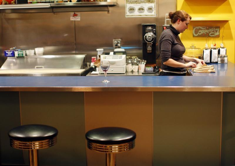 A waitress stands behind the counter at AS220 Restaurant in Providence