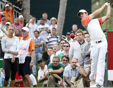 Tennis star Caroline Wozniacki watches her boyfriend Rory McIlroy of Northern Ireland as he tees off on the 16th hole during the final round of the 2014 Omega Dubai Desert Classic in Dubai