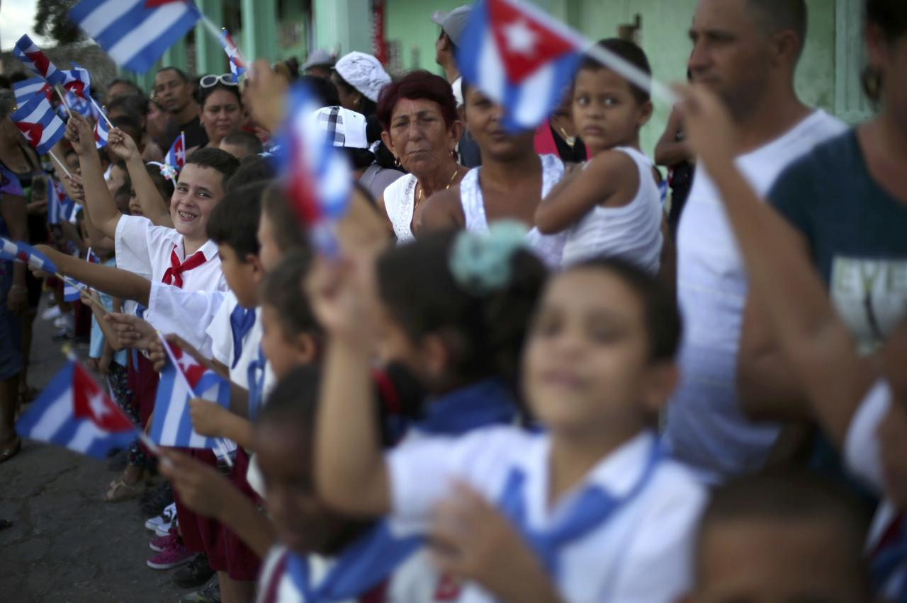 People wave Cuban flags as they await the arrival of the caravan carrying the late Cuban President Fidel Castro's ashes in El Maja, Cuba, December 1, 2016.   REUTERS/Edgard Garrido TPX IMAGES OF THE DAY