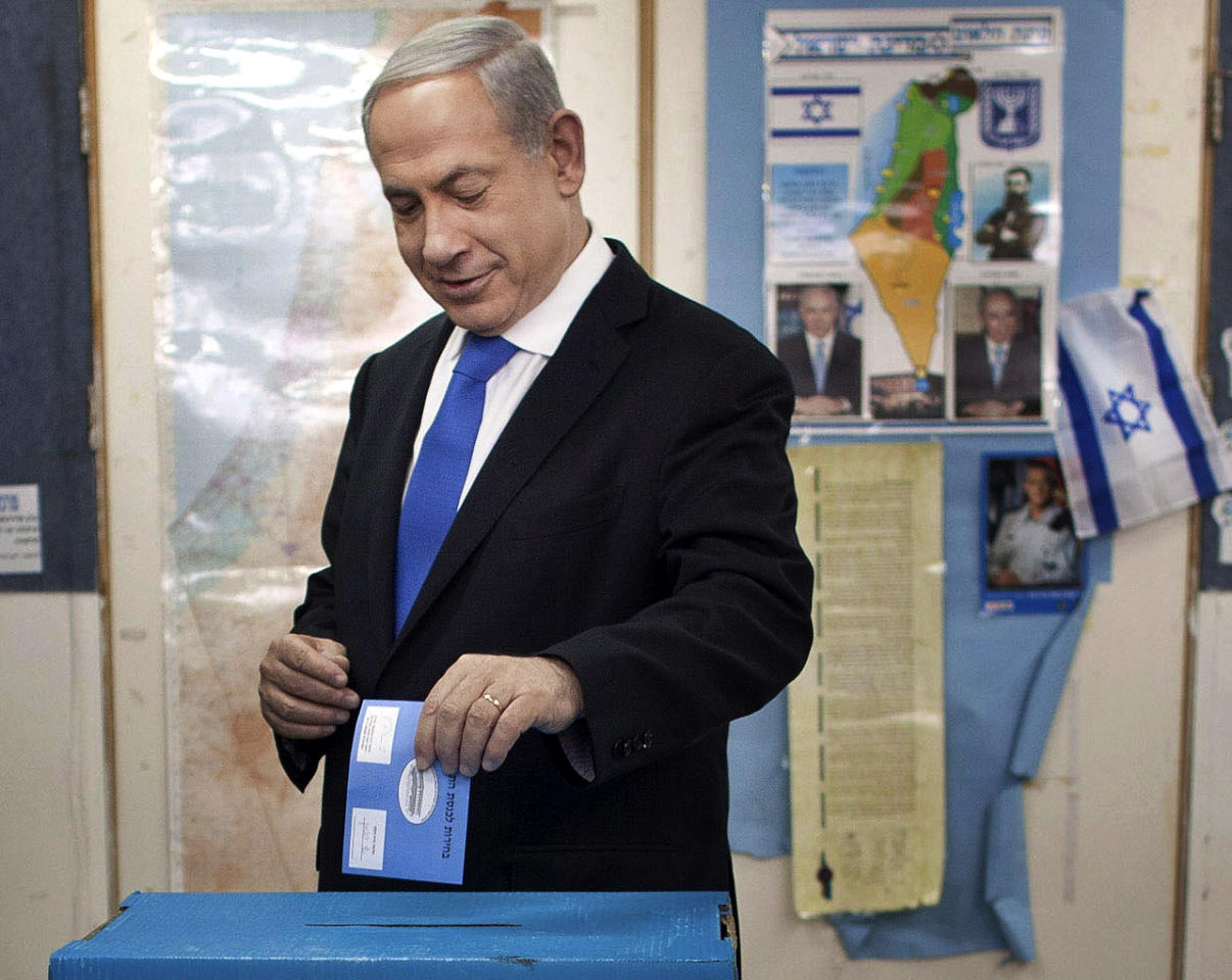 Israeli Prime Minister Benjamin Netanyahu casts his ballottogether with his wife Sara, left and sons Yair and Avner, background left, at a polling station in Jerusalem, Tuesday, Jan. 22, 2013.Israelis headed to polling stations Tuesday to cast votes in a parliamentary election expected to return Netanyahu to office despite years of stalled peacemaking with the Palestinians and mounting economic troubles. (AP Photo/Uriel Sinai, Pool)