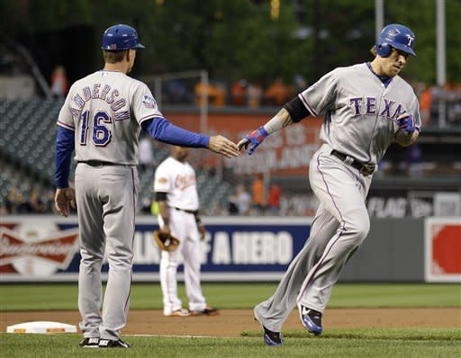 Texas Rangers' Josh Hamilton, right, high-fives third base coach Dave Anderson as he rounds the bases after hitting a two-run home run in the first inning of a baseball game against the Baltimore Orioles in Baltimore, Tuesday, May 8, 2012. (AP Photo/Patrick Semansky)