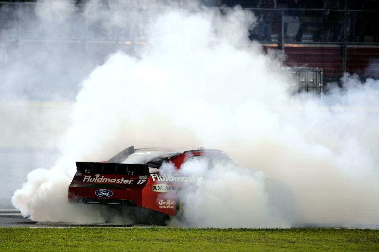 CHARLOTTE, NC - OCTOBER 15:  Matt Kenseth, driver of the #17 Fluidmaster Ford, celebrates with a burnout after winning the NASCAR Sprint Cup Series Bank of America 500 at Charlotte Motor Speedway on October 15, 2011 in Charlotte, North Carolina.  (Photo by Jared C. Tilton/Getty Images for NASCAR)
