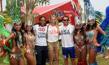 Jul 23, 2016; Los Angeles, CA, USA; American basketball player Tamika Catchings (third from left) and American volleyball player Kerri Walsh-Jennings (center) and American water polo player Tony Azevedo (third from right) pose with samba dancers during the Team USA Road to Rio tour at Venice Beach. Mandatory Credit: Kelvin Kuo-USA TODAY Sports