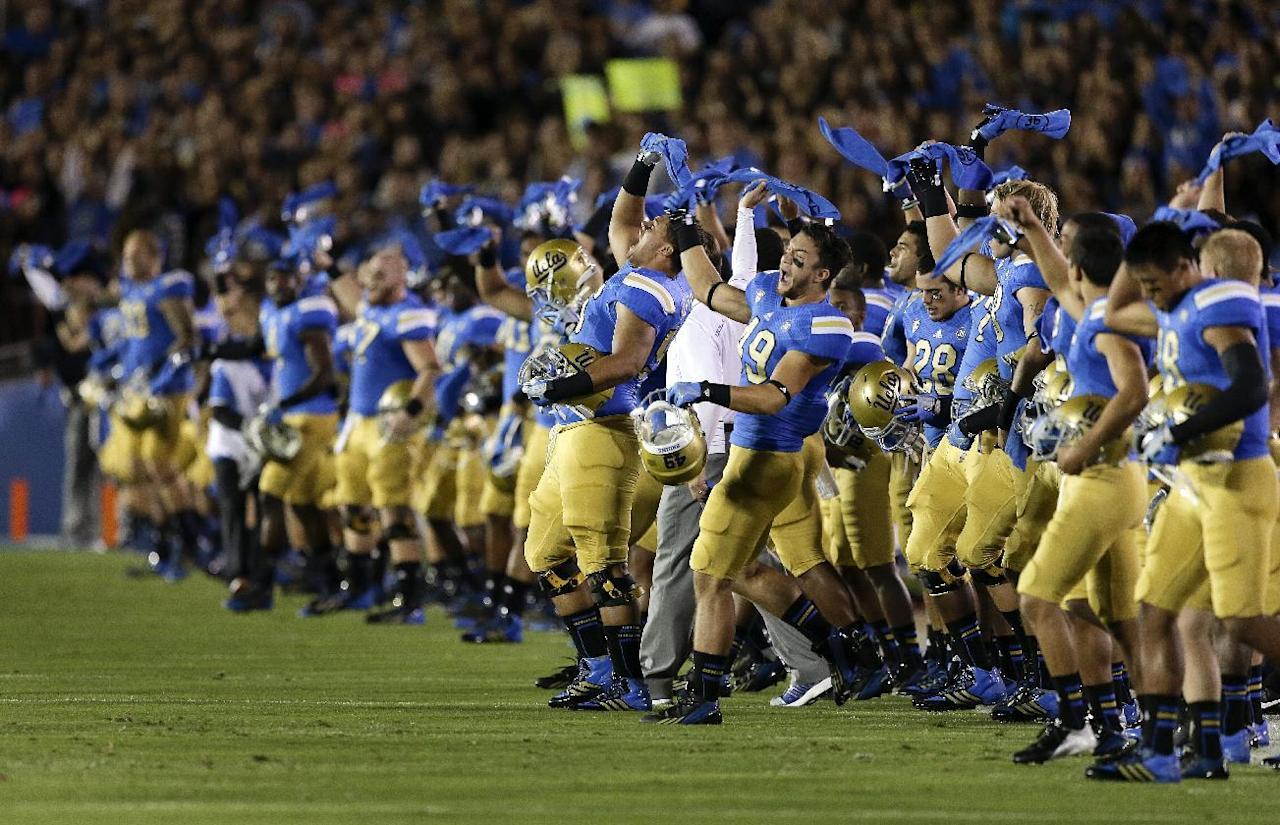 Members of the UCLA team cheer after a moment of silence for UCLA wide receiver Nick Pasquale before an NCAA college football game against New Mexico State Saturday, Sept. 21, 2013, in Pasadena, Calif. Pasquale was struck and killed by a car Sept. 8 in San Clemente, Calif. (AP Photo/Chris Carlson)