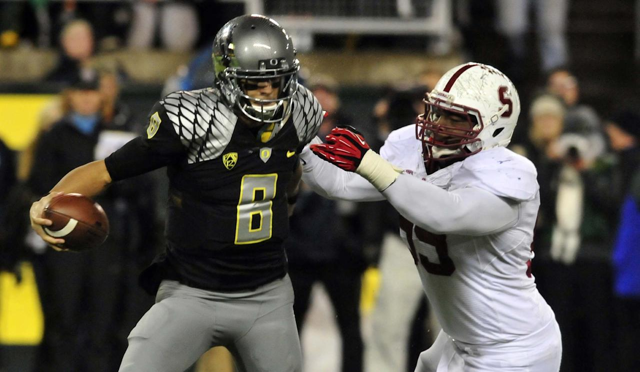 EUGENE, OR - NOVEMBER 17: Quarterback Marcus Mariota #8 of the Oregon Ducks eludes the rush of defensive tackle Terrence Stephens #99 of the Stanford Cardinal during the first quarter of the game at Autzen Stadium on November 17, 2012 in Eugene, Oregon. (Photo by Steve Dykes/Getty Images)