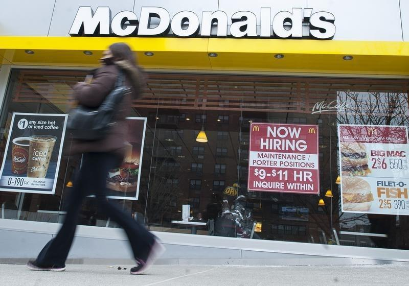 A passersby walks in front of a help wanted sign at a McDonalds restaurant in the Brooklyn borough of New York