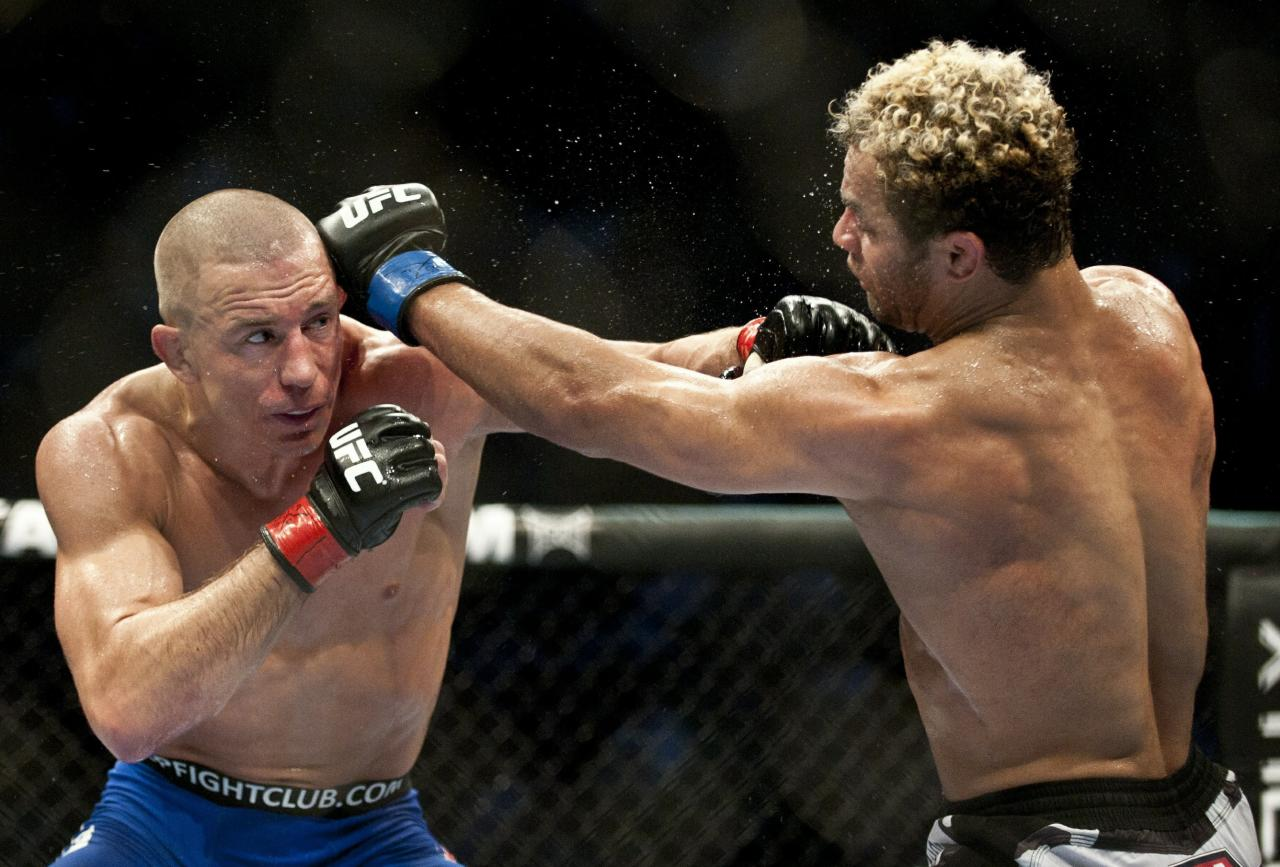 Georges St-Pierre (L) from Montreal, Canada battling with Josh Koscheck from Waynesburg US on the third round during the Ultimate Fighting Championship on December 11, 2010 at Bell Centre in Montreal, Quebec, Canada.    AFP PHOTO / ROGERIO BARBOSA  (Photo credit should read ROGERIO BARBOSA/AFP/Getty Images)