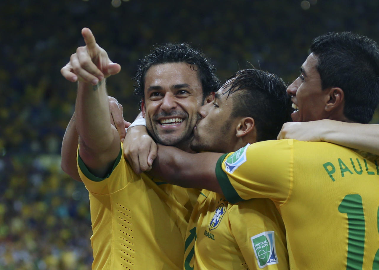 Brazil's Fred is congratulated by Neymar, center and Paulinho after scoring his side's 3rd goal against Spain during the soccer Confederations Cup final match at the Maracana stadium in Rio de Janeiro, Brazil, Sunday, June 30, 2013. (AP Photo/Andre Penner)