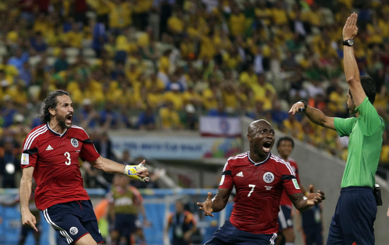 Colombia's Mario Yepes, left, and Pablo Armero remonstrate with referee Carlos Velasco Carballo from Spain after he disallowed a goal during the World Cup quarterfinal soccer match between Brazil and Colombia at the Arena Castelao in Fortaleza, Brazil, Friday, July 4, 2014