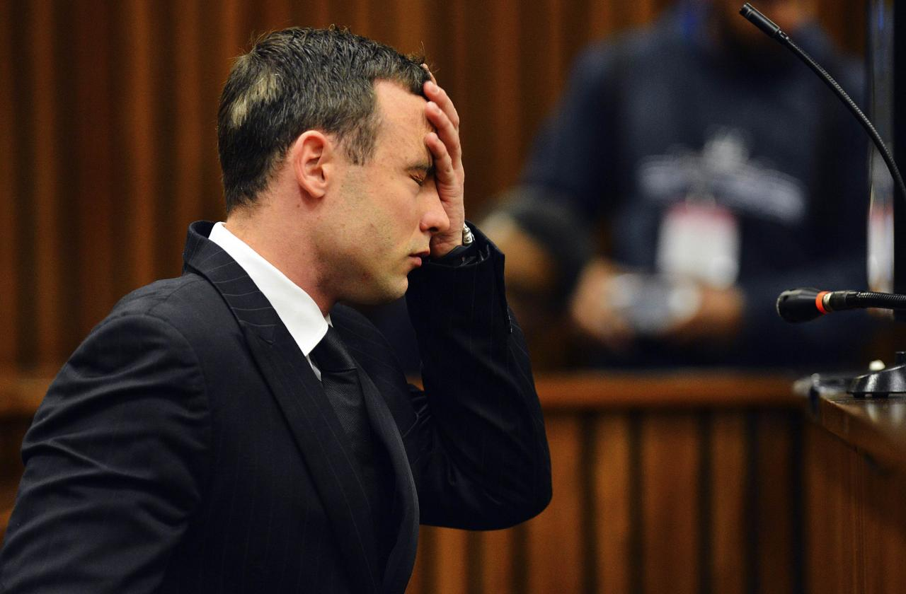 South African Olympic and Paralympic athlete Oscar Pistorius reacts in the dock during his murder trial in the North Gauteng High Court in Pretoria June 30, 2014. Pistorius is on trial for murdering his girlfriend Reeva Steenkamp at his suburban Pretoria home on Valentine's Day last year. REUTERS/Phill Magakoe/Pool (SOUTH AFRICA - Tags: SPORT CRIME LAW ATHLETICS)