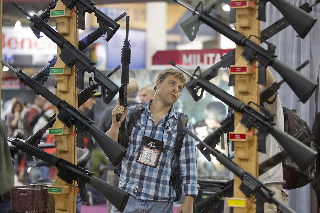 Michael Kiefer, of DeFuniak Springs, Fla., checks out a display of rifles at the Rock River Arms booth.