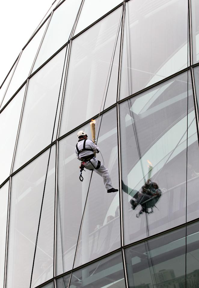 GATESHEAD, UNITED KINGDOM - JUNE 16:  In this handout image provided by LOCOG, Torchbearer Richard Jackson abseils down The Sage building in Gateshead carrying the Olympic Flame on the Torch Relay leg through Gateshead on June 16, 2012 in Gateshead, England. The Olympic Flame is now on day 29 of a 70-day relay involving 8,000 torchbearers covering 8,000 miles.  (Photo by LOCOG via Getty Images)