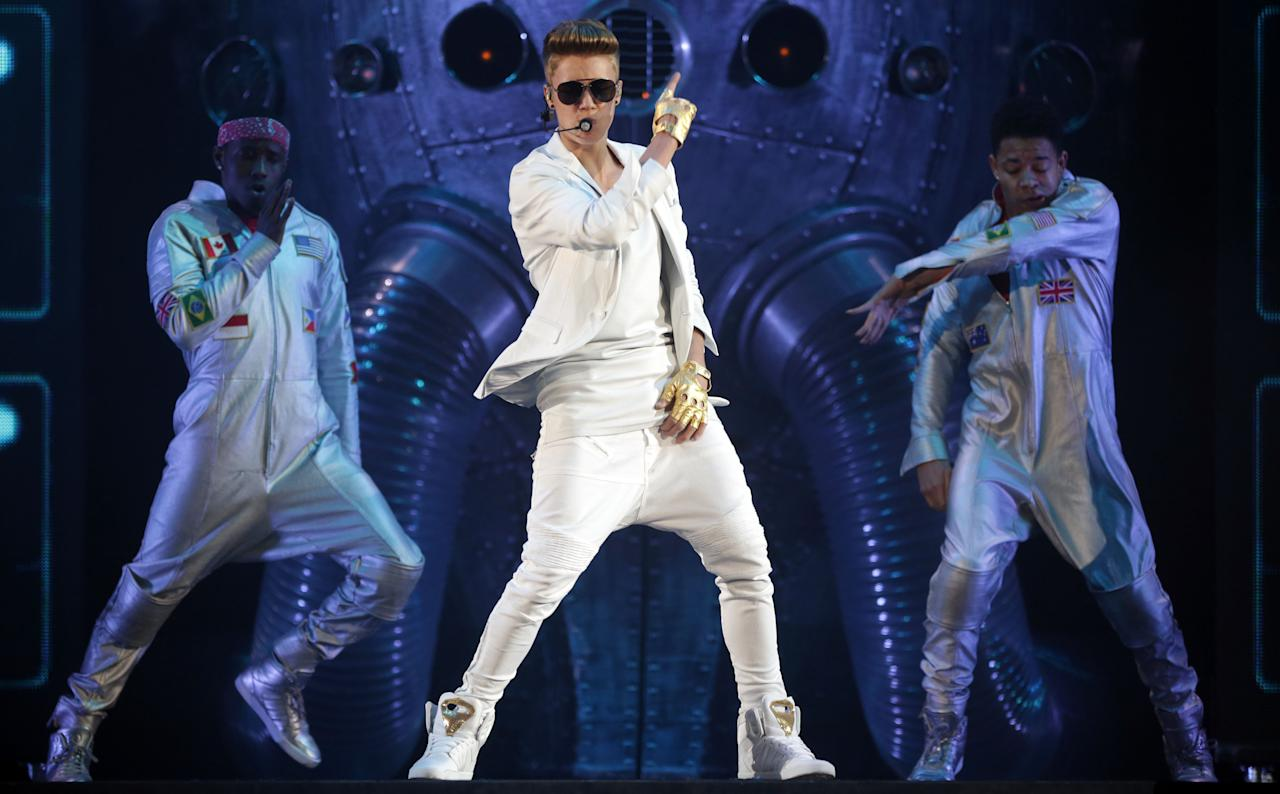 """FILE - In this March 28, 2013 file picture Canadian singer Justin Bieber performs on stage during the """"I Believe Tour """" in Munich, southern Germany. A German official says Justin Bieber had to leave a monkey in quarantine after arriving in the country last week without the necessary papers for the animal. The 19-year-old singer arrived at Munich airport last Thursday. Customs spokesman Thomas Meister said Saturday March 30, 2013 that when he went through customs he didn't have the documentation necessary to bring the capuchin monkey into the country - so the animal had to stay with authorities. (AP Photo/Matthias Schrader,File)"""