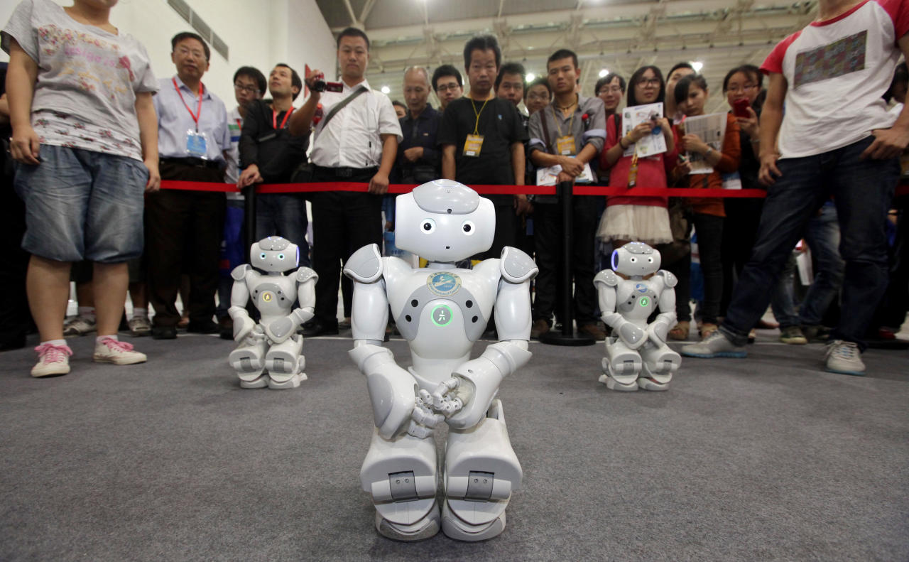Robots, made by students from Wuhan Institute of Technology University, dance for the visitors at the 13th China International Machinery and Electronic Products Expo in Wuhan, Hubei province, September 23, 2012. REUTERS/Darley Shen (CHINA - Tags: SOCIETY SCIENCE TECHNOLOGY BUSINESS) CHINA OUT. NO COMMERCIAL OR EDITORIAL SALES IN CHINA