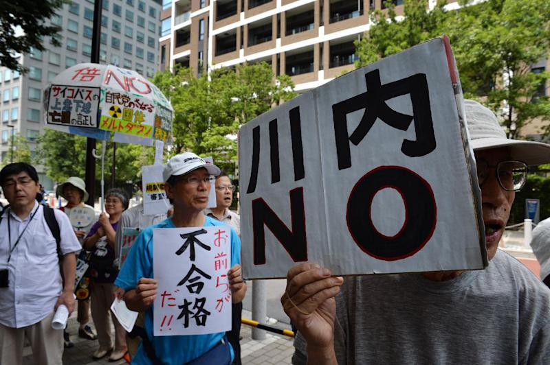 "An anti-nuclear protester holds a placard reading ""Sendai NO"" during a rally in Tokyo on July 16, 2014"