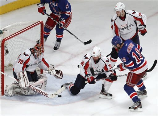 Washington Capitals goalie Braden Holtby (70) blocks a shot by New York Rangers right wing Marian Gaborik (10) as Capitals left wing Matt Hendricks (26) defends and Capitals defenseman John Carlson (74) watches during the second period of Game 5 the NHL hockey Stanley Cup playoffs Eastern Conference semifinals at Madison Square Garden in New York, Monday, May 7, 2012. (AP Photo/Kathy Willens)