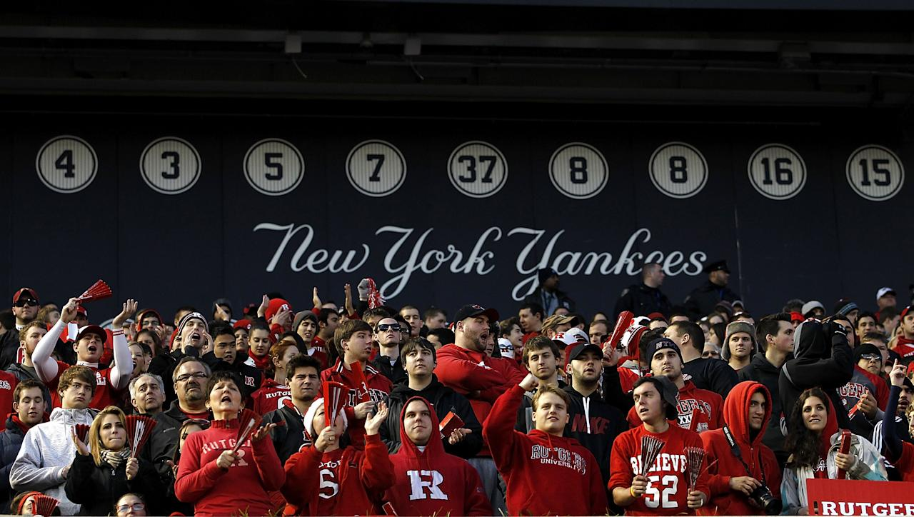 NEW YORK - DECEMBER 30:  Fans of the Rutgers Scarlet Knights cheer in front of the wall of retired New York Yankees numbers during the New Era Pinstripe Bowl against the Iowa State Cyclones at Yankee Stadium on December 30, 2011 in the Bronx Borough of New York City.  (Photo by Jeff Zelevansky/Getty Images)