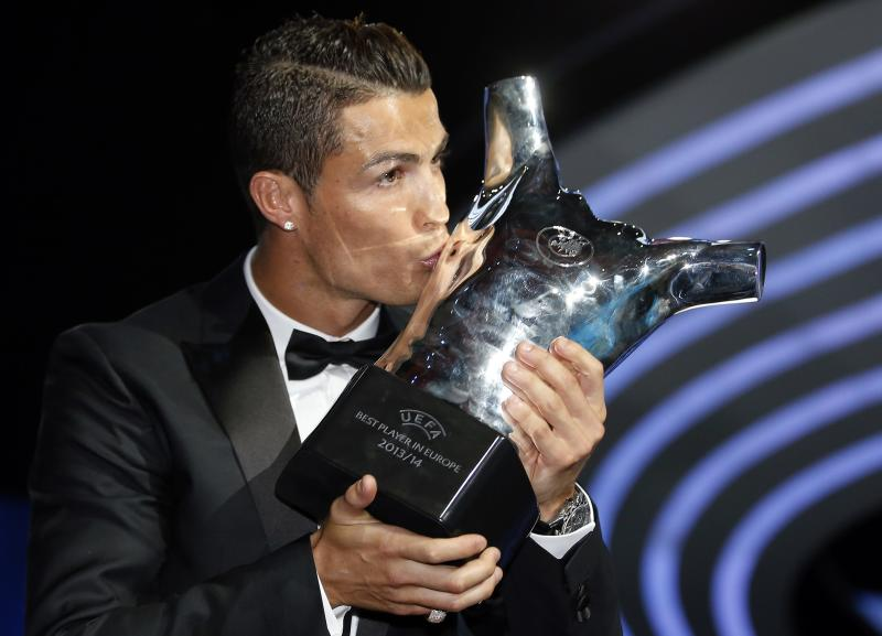 Real Madrid's Cristiano Ronaldo kisses his Best Player UEFA 2014 Award during the draw ceremony for the 2014/2015 Champions League Cup soccer competition in Monaco