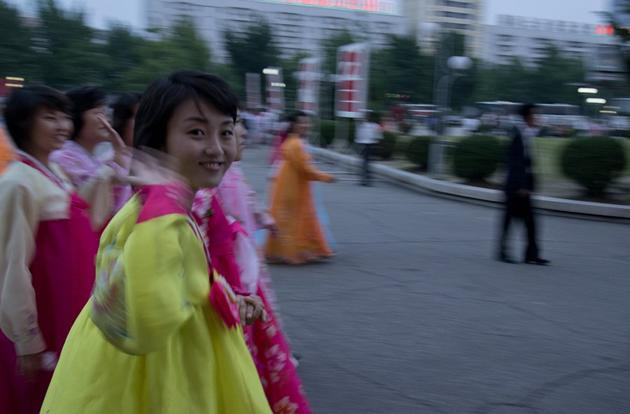 A woman wearing a Choson-ot (or a Hanbok as it's called in South Korea) waves to the camera after a mass dance on National Day.