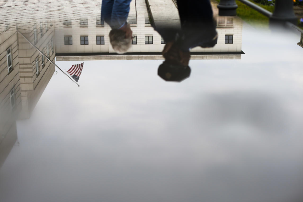 United States security officers and the United States embassy with the U.S. flag are reflected in a rain puddle in Berlin, Tuesday, April 16, 2013. On Monday April 15, 2013 two bombs exploded in the crowded streets at the Boston marathon in the United States. (AP Photo/Markus Schreiber)