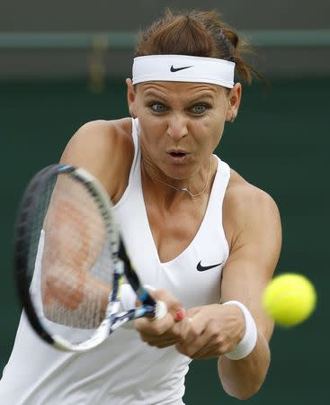 Safarova of Czech Republic hits a return to Cibulkova of Slovakia during their women's singles tennis match at the Wimbledon Tennis Championships, in London