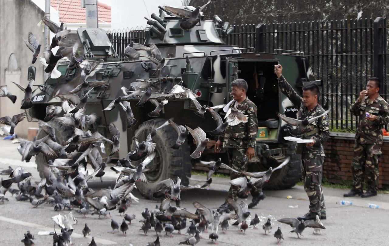 Government soldiers of Task Force Zamboanga feed pigeons with bread crumbs near a military command post during a lull in fighting with Muslim rebels of Moro National Liberation Front (MNLF), in Zamboanga city in southern Philippines September 16, 2013. REUTERS/Erik De Castro (PHILIPPINES - Tags: CIVIL UNREST CONFLICT POLITICS MILITARY ANIMALS)