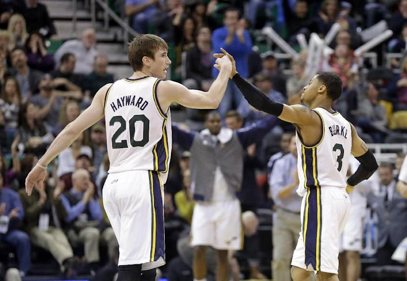 Utah Jazz's Gordon Hayward (20) and teammate Trey Burke (3) celebrate on the court in the fourth quarter during an NBA basketball game against the Washington Wizards Saturday, Jan. 25, 2014, in Salt Lake City. The Jazz won 104-101