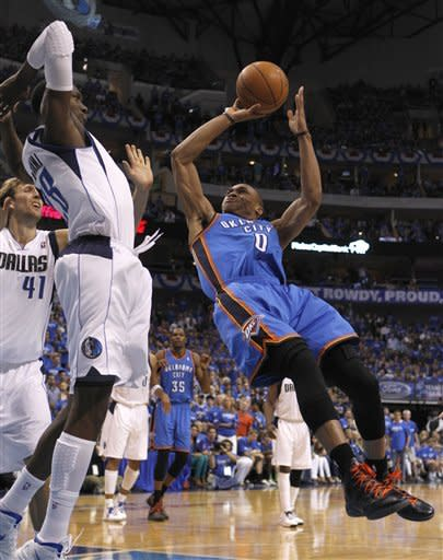 Oklahoma City Thunder point guard Russell Westbrook (0) shoots against Dallas Mavericks center Ian Mahinmi (28) and  forward Dirk Nowitzki (41) of Germany during the first half of Game 4 in a first-round NBA basketball playoff series, Saturday, May 5, 2012, in Dallas. (AP Photo/LM Otero)