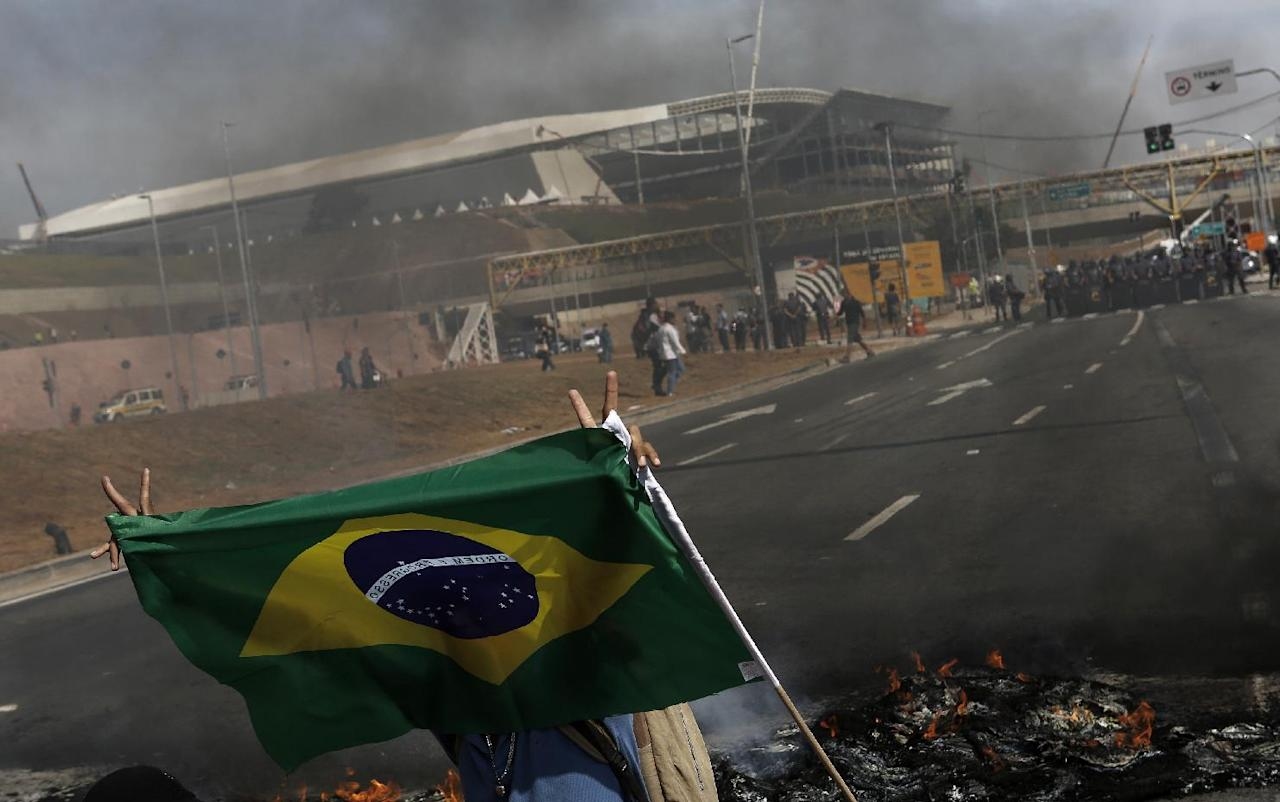 A member of Brazil's Homeless Workers' Movement blocks a road during a protest in front of Sao Paulo's World Cup stadium in this May 15, 2014 file photo. With kickoff two weeks away and tensions simmering over the costs of hosting the month-long soccer event, some are showing their anger by saying they will root against the national team, perhaps Brazil's most prominent symbol on the global stage. REUTERS/Nacho Doce/Files (BRAZIL - Tags: SPORT SOCCER WORLD CUP CIVIL UNREST)