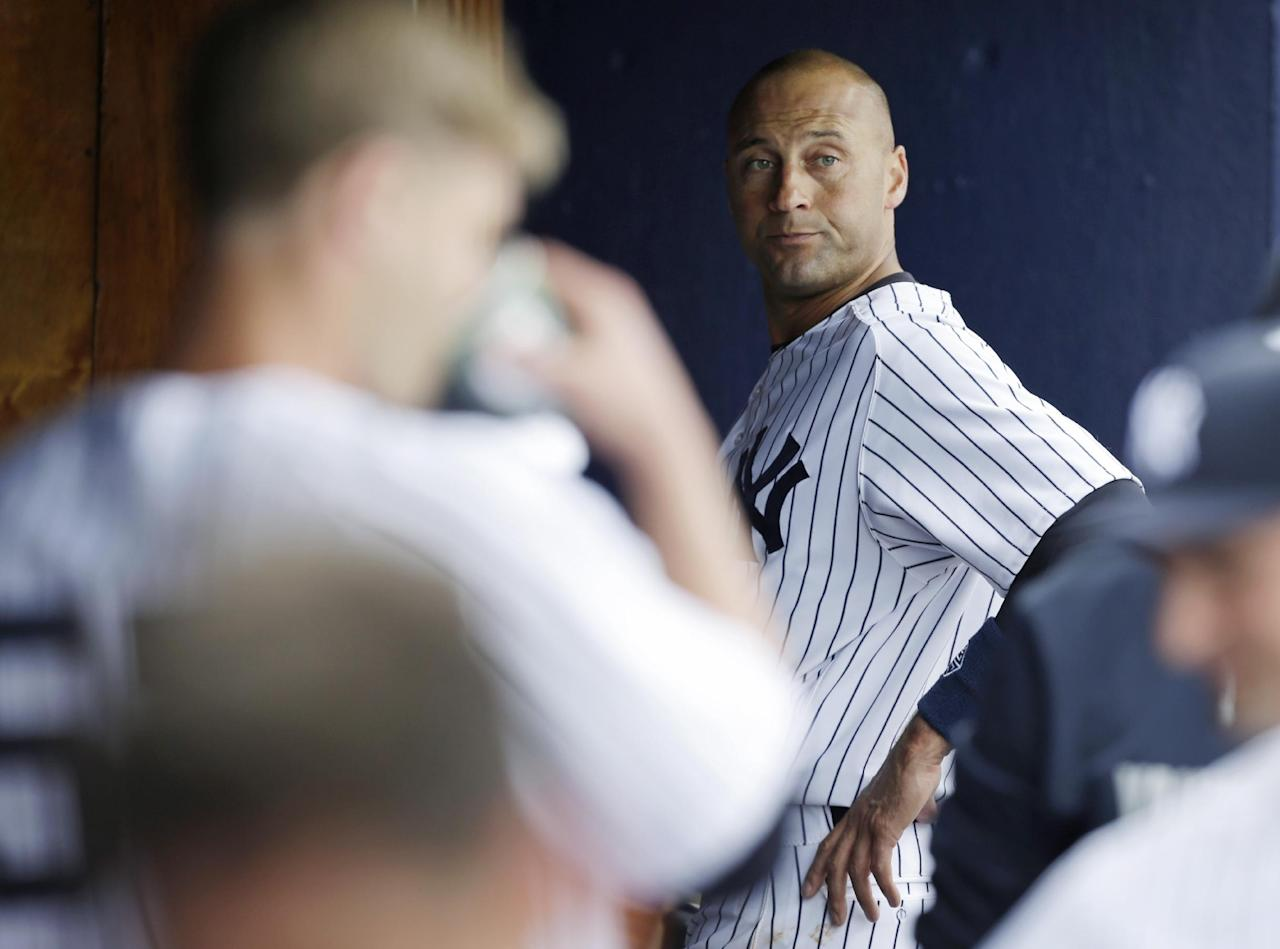 New York Yankees shortstop Derek Jeter, right, stands in the dugout during an exhibition baseball game against the Pittsburgh Pirates Thursday, Feb. 27, 2014, in Tampa, Fla. (AP Photo/Charlie Neibergall)