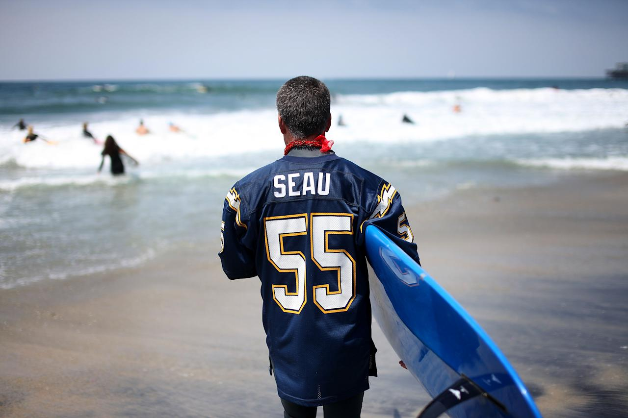 "OCEANSIDE, CA - MAY 6: A surfer prepares go out into the surf for a ceremony during a ""paddle-out"" in honor of NFL star Junior Seau on May 6, 2012 in Oceanside, California.  Seau, who played for various NFL teams including the San Diego Chargers, Miami Dolphins and New England Patriots was found dead in his home on May 2nd of an apparent suicide.  Family members have decided to donate his brain for research on links between concussions and possible depression. (Photo by Sandy Huffaker/Getty Images)"