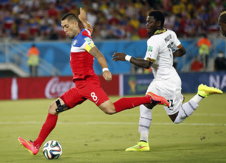 Dempsey of the U.S. shoots to score a goal past Ghana's Muntari during their 2014 World Cup Group G soccer match at the Dunas arena in Natal
