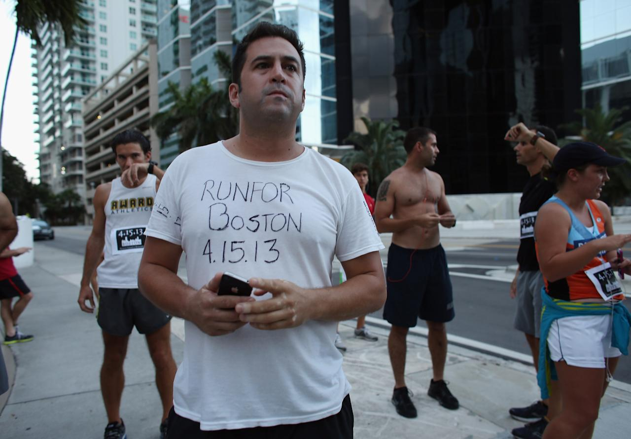 """MIAMI, FL - APRIL 16:  Runner Lalo Senior wears a shirt where he wrote """"RunFor Boston 4.15.13,"""" as the Baptist Health South Florida Brickell Run Club honors the victims of the Boston Marathon bombings on April 16, 2013 in Miami, Florida. The event drew approximately 1,000 people who wanted to honor the three people killed in the Boston bombing as well as the over one hundred who were injured.  (Photo by Joe Raedle/Getty Images)"""