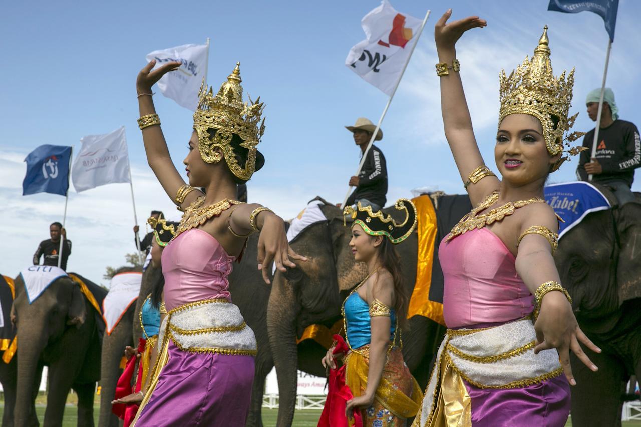 HUA HIN, THAILAND - AUGUST 28: Thai dancers perform during an opening ceremony for the King's Cup Elephant Polo tournament on August 28, 2013 in Hua Hin, Thailand. This is the 12th year for the event. The sport of elephant polo started in Nepal in 1982. Proceeds from the tournament go to help rehabilitate elephants rescued from abuse. Each team has three players and three elephants. Matches take place on a pitch (field) 80 meters by 48 meters using standard polo balls. The game is divided into two 7 minute 'chukkas' or halves. There are 16 teams in this year's tournament, including one team of transgendered 'ladyboys'. (Photo by Paula Bronstein/Getty Images)