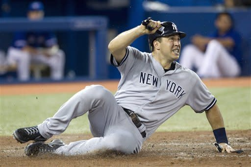 New York Yankees' Mark Teixeira safely makes it to home plate to score after Jayson Nix hit a single off Toronto Blue Jays starting pitcher Aaron Laffey during  the fourth inning of a baseball game in Toronto on Saturday, Aug. 11 , 2012. (AP Photo/The Canadian Press, Chris Young)