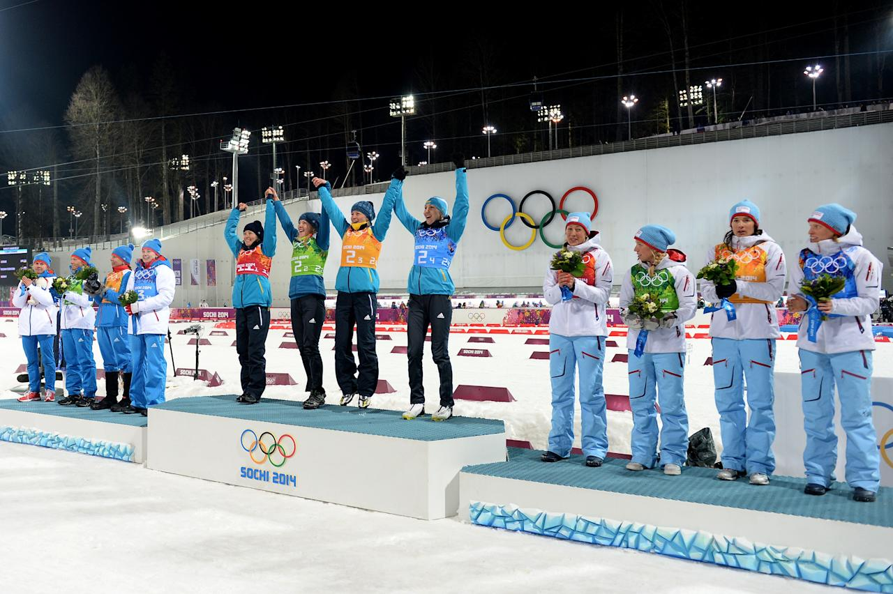 SOCHI, RUSSIA - FEBRUARY 21: (L-R) Silver medalists Yana Romanova, Olga Zaitseva, Ekaterina Shumilova and Olga Vilukhina of Russia, gold medalists Vita Semerenko, Juliya Dzhyma, Valj Semerenko and Olena Pidhrushna of Ukraine and bronze medalists Fanny Welle-Strand Horn, Tiril Eckhoff, Ann Kristin Aafedt Flatland and Tora Berger of Norway celebrate on the podium during the flower ceremony for the the Biathlon Women's 4 x 6 km Relay during day 14 of the Sochi 2014 Winter Olympics at Laura Cross-country Ski & Biathlon Center on February 21, 2014 in Sochi, Russia. (Photo by Harry How/Getty Images)