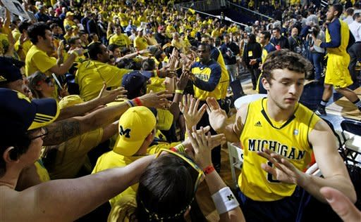 Michigan guard Zack Novak, right, high-fives fans after warmups before an NCAA college basketball game against Ohio State, Saturday, Feb. 18, 2012, in Ann Arbor, Mich. (AP Photo/Tony Ding)