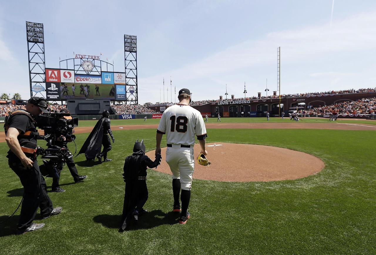Miles Scott, dressed as Batkid, second from right, walks to the mound with San Francisco Giants pitcher Matt Cain (18) to throw the ceremonial first pitch before a home opener baseball game between the Giants and the Arizona Diamondbacks in San Francisco, Tuesday, April 8, 2014. On Nov. 15, 2013, Scott, a Northern California boy with leukemia, fought villains and rescued a damsel in distress as a caped crusader through The Greater Bay Area Make-A-Wish Foundation. (AP Photo/Eric Risberg, Pool)