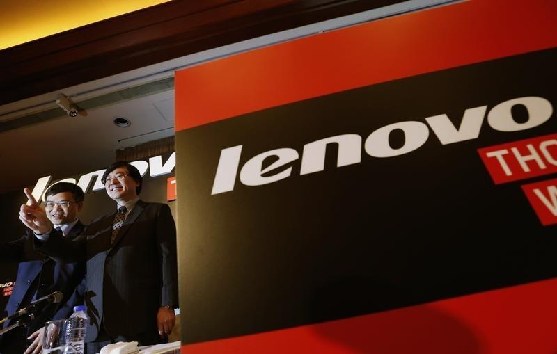Lenovo Chairman and CEO Yang gestures beside CFO Wong during a news conference in Hong Kong