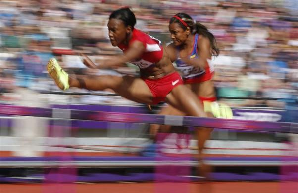 Kellie Wells of the U.S. (L) and Colombia's Lina Florez compete in their women's 100m hurdles round 1 heat during the London 2012 Olympic Games at the Olympic Stadium August 6, 2012.