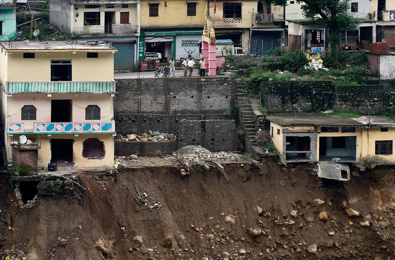Damaged houses are seen precariously above the flash flood-eroded Mandakini river in the town of Tilwara, around 30kms from Rudraprayag, on June 26, 2013. Around 1,000 people have been killed in flash floods and landslides in northern India, as a top official warned June 24 that rebuilding of the devastated Himalayan region would take years.   AFP PHOTO/MANAN VATSYAYANA