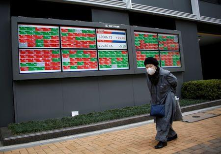 A woman walks past electronic boards showing stock prices outside a brokerage in Tokyo