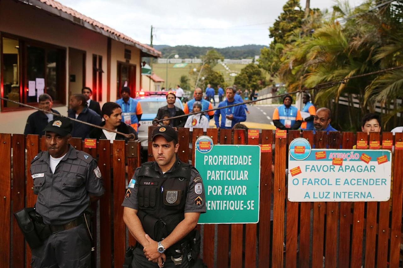 Police officers stand guard at the entrance of the Granja Comary training center, during a teachers's protest in front of  where the Brazilian national soccer team will train and reside during the World Cup, in Rio de Janeiro, Brazil, Monday, May 26, 2014. Demonstrators are protesting against the money being spent by the government on the World Cup. (AP Photo/Leo Correa)