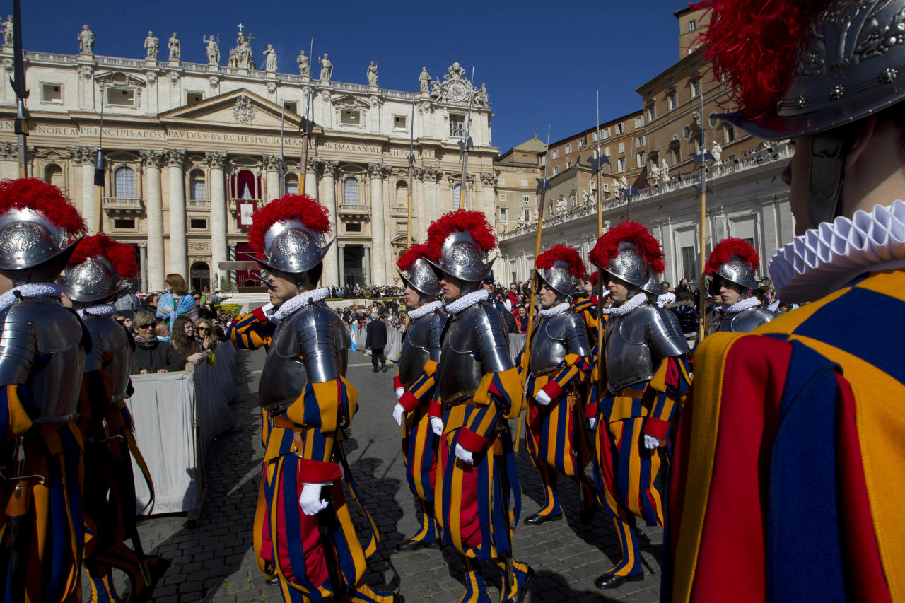 Vatican Swiss Guards parade in St. Peter's Square ahead of Pope Francis' Easter Sunday Mass in St. Peter's Square at the Vatican Sunday, April 20, 2014. Even before Mass began in late morning, more than 100,000 tourist, Romans and pilgrims, young and old, had turned out for the Mass. Many more streamed in throughout the ceremony, and the broad boulevard leading from the square to the Tiber river filled up with the faithful and the curious, trying to catch a glimpse of the pontiff at the altar under a canopy erected on the steps of St. Peter's Basilica. (AP Photo/Andrew Medichini)