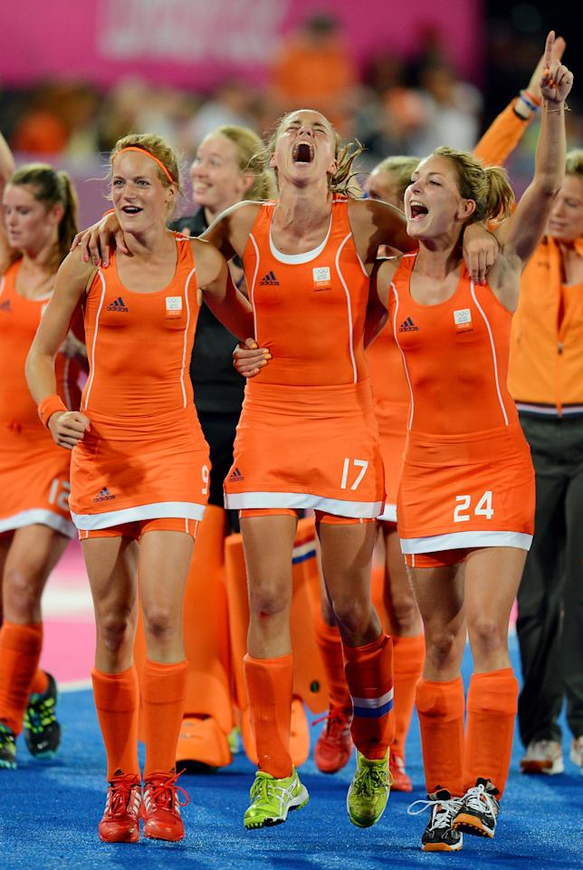 LONDON, ENGLAND - AUGUST 10:  Carlien Dirkse Van Den Heuvel #9, Maartje Paumen #17 and Eva De Goede #24 of Netherlands celebrate their 2-0 victory over Argentina to win the Women's Hockey gold medal match on Day 14 of the London 2012 Olympic Games at Hockey Centre on August 10, 2012 in London, England.  (Photo by Mike Hewitt/Getty Images)