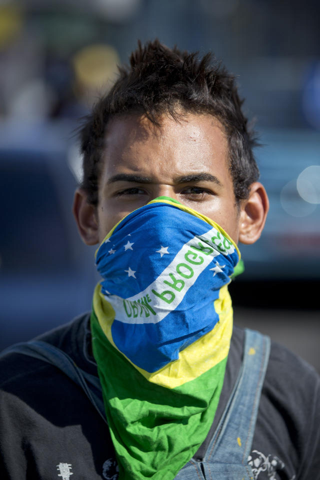 A protestor with a Brazilian flag covering his face stands on the main road leading to the Castelao stadium before the start of a soccer Confederations Cup group B match between Nigeria and Spain in Fortaleza, Brazil, Sunday, June 23, 2013. Small gatherings occurred Sunday in a few cities, no clashes were reported. On Saturday a quarter-million Brazilians protested in more than 100 cities, but the gatherings were less violent than those seen earlier in the week. (AP Photo/Victor R. Caivano)